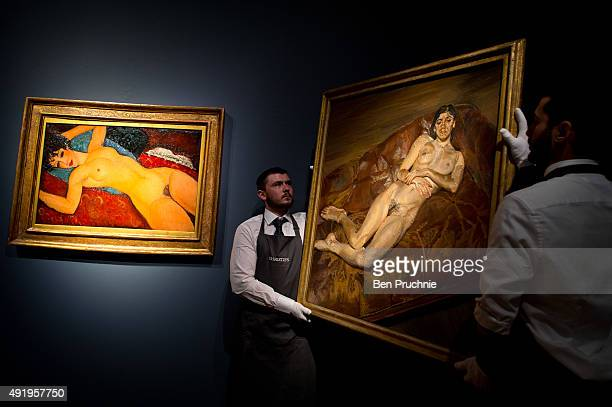Art handlers hang the painting 'Naked Bella Freud' by artist Lucien Freud next to Amedeo Modigliani's 'Nu couche' during the preview ahead of the...