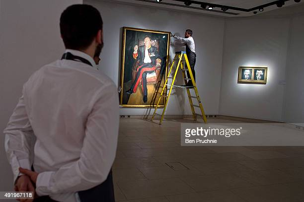 Art handlers hang the painting 'The Brigadier' by artist Lucian Freud during the preview ahead of the artist's muse a curated evening sale during...
