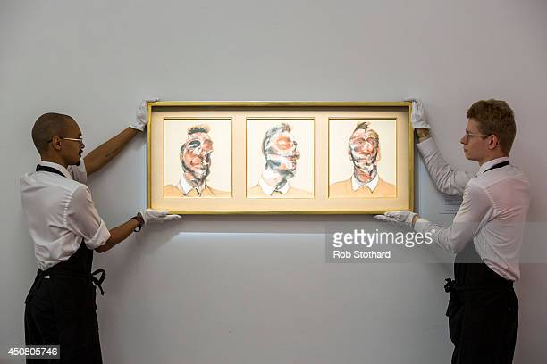 Art handlers pose with Francis Bacon's 1964 piece Three Studies for Portrait of George Dyer estimated to sell for £15£20 million on display at...