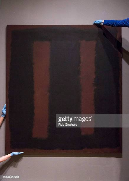 Art handlers pose with Mark Rothko's painting Black On Maroon 1958 after going back on display at Tate Modern gallery 18 months after it was...