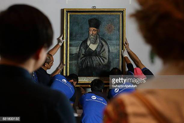 Art handlers prepare to install the painting of Matteo Ricci by artist Emmanuele Pereira at the Asian Civilisations Museum on May 17 2016 in...