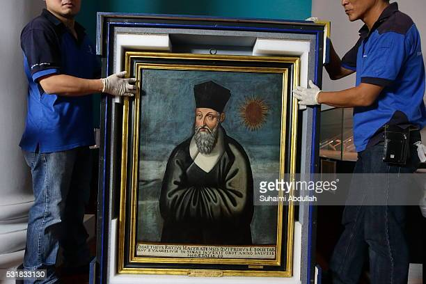 Art handlers unbox the painting of Matteo Ricci by artist Emmanuele Pereira at the Asian Civilisations Museum on May 17 2016 in Singapore The oil on...