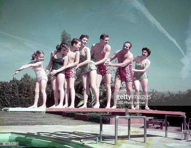 from left Diane Sharon Robert Dawn Jack Art and Lois posing on a diving board at a swimming pool 1957