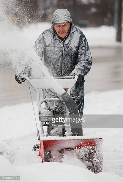 TORONTO ON FEBRUARY 18 Art Molasy owner of ABM Garage on Lakeshore Blvd Mississauga gets covered in blown snow as he plows the parking lot in front...