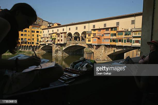 Art students paint next to the Ponte Vecchio bridge on July 10 2013 in Florence Italy The region of Tuscany is among Italy's biggest tourist...