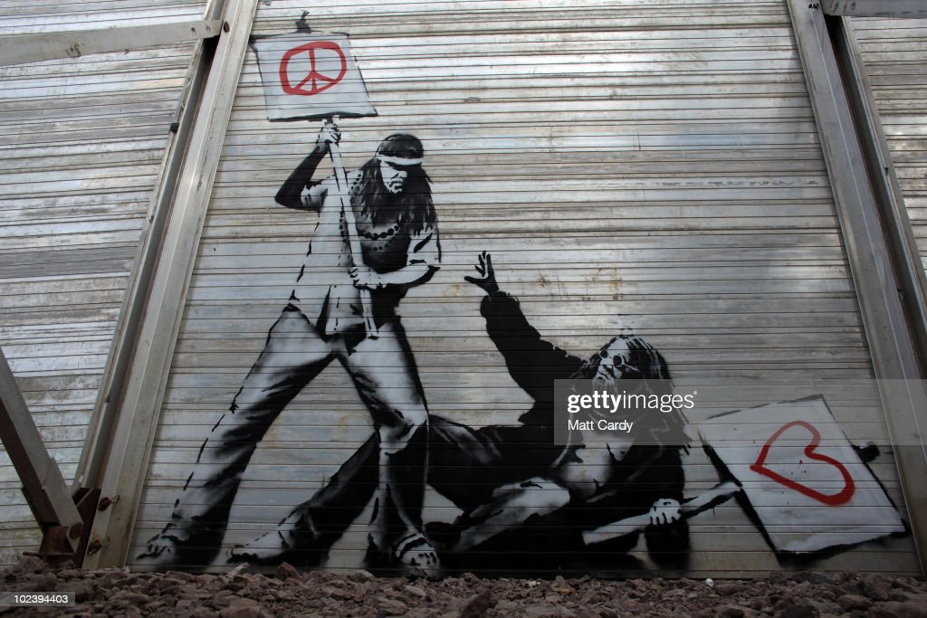 Art work said to be by underground artist Banksy is seen on the fence at the Glastonbury Festival site at Worthy Farm, Pilton on June 24, 2010 in Glastonbury, England. The gates opened yesterday to what has become Europe's largest music festival and is celebrating its 40th anniversary.