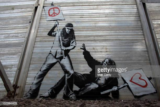 Art work said to be by underground artist Banksy is seen on the fence at the Glastonbury Festival site at Worthy Farm Pilton on June 24 2010 in...