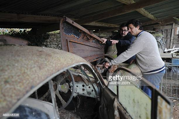 Artcurial Motorcars managing director Matthieu Lamoure and expert Pierre Novikov check a model on November 26 2014 at the Gaillard property in the...
