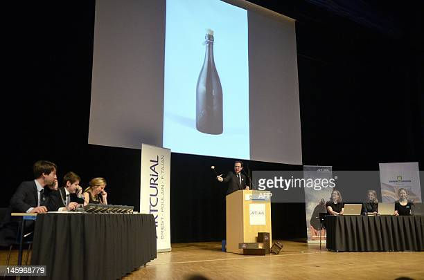 Artcurial's Auctioneer Arnaud Oliveux auctions a bottle of champagne in Mariehamn aland on June 8 2012 A 200yearold bottle of Veuve Clicquot...
