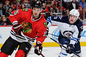 Artem Anisimov of the Chicago Blackhawks and Andrew Copp of the Winnipeg Jets watch for the puck in the first period of the NHL game at the United...