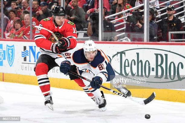Artem Anisimov of the Chicago Blackhawks and Yohann Auvitu of the Edmonton Oilers chase the puck in the first period at the United Center on October...