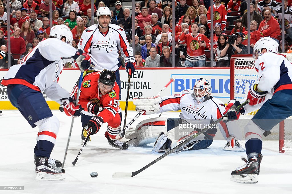 Artem Anisimov of the Chicago Blackhawks dives for the puck in front of Alex Ovechkin and goalie Braden Holtby of the Washington Capitals in the...