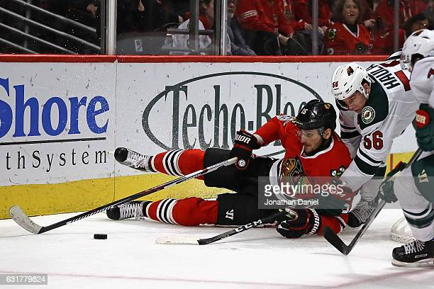 Artem Anisimov of the Chicago Blackhawks falls to the ice while batting for the puck with Erik Haula of the Minnesota Wild at the United Center on...