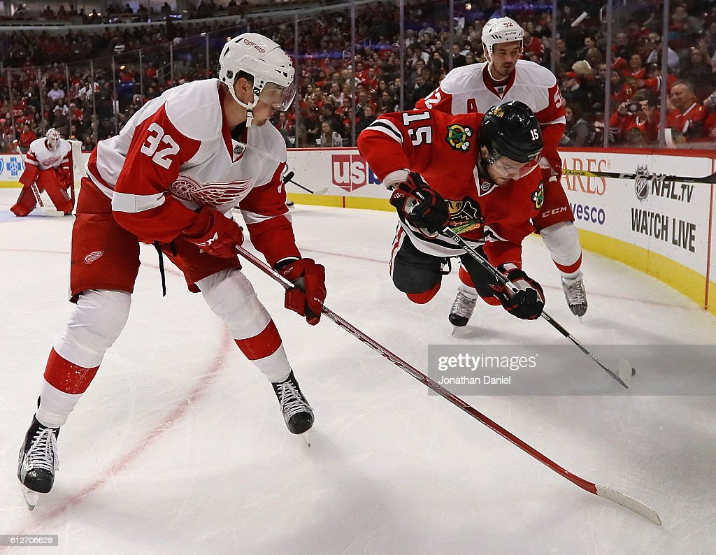 Artem Anisimov #15 of the Chicago Blackhawks gets arborne trying control the puck between Louis-Marc Aubry #32 and Jonathan Ericsson #52 of the Detroit Red Wings during a preseason game at the United Center on October 4, 2016 in Chicago, Illinois.