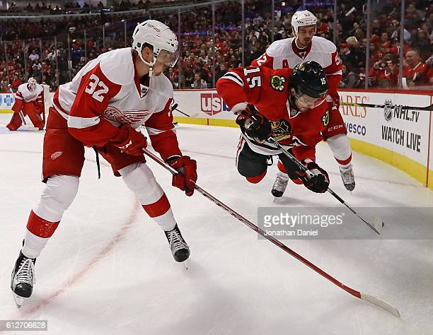 Artem Anisimov of the Chicago Blackhawks gets arborne trying control the puck between LouisMarc Aubry and Jonathan Ericsson of the Detroit Red Wings...