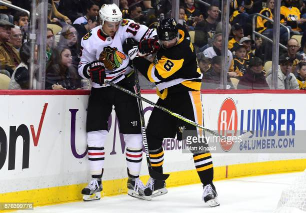 Artem Anisimov of the Chicago Blackhawks is checked into the boards by Brian Dumoulin of the Pittsburgh Penguins at PPG PAINTS Arena on November 18...