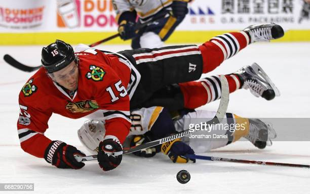 Artem Anisimov of the Chicago Blackhawks is tripped by Viktor Arvidsson of the Nashville Predators in Game One of the Western Conference First Round...