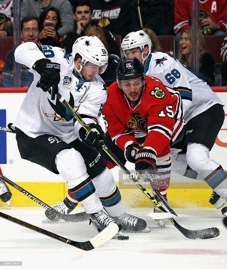 Artem Anisimov of the Chicago Blackhawks knocks the puck away from Chris Tierney of the San Jose Sharks at the United Center on February 9 2016 in...