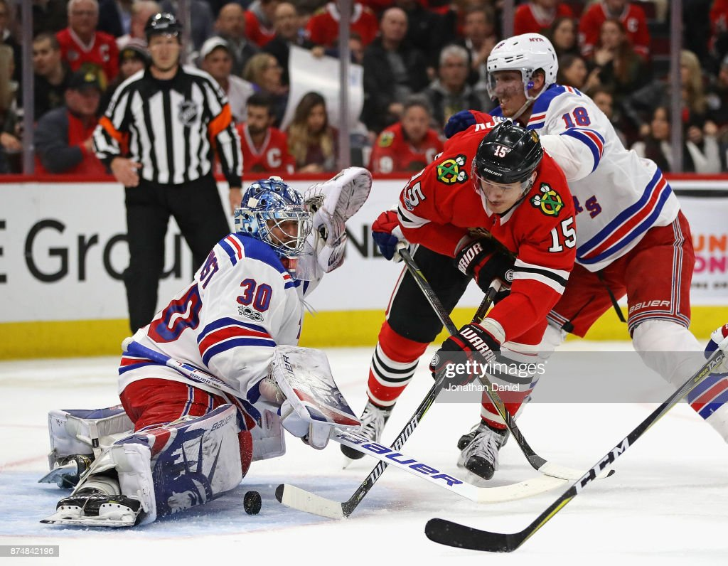 Artem Anisimov #15 of the Chicago Blackhawks, pressured by Marc Staal #18 of the New York Rangers, scores his second goal chasing Henrik Lundqvist #30 from the game in the third period at the United Center on November 15, 2017 in Chicago, Illinois. The Blackhwks defeated the Rangers 6-3.