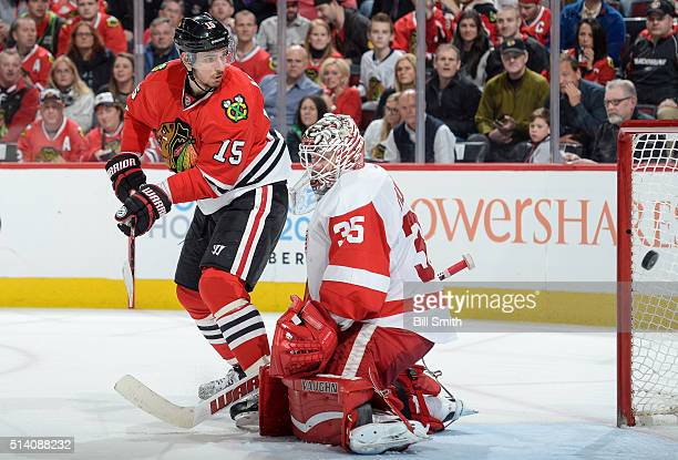 Artem Anisimov of the Chicago Blackhawks scores on goalie Jimmy Howard of the Detroit Red Wings in the third period of the NHL game at the United...