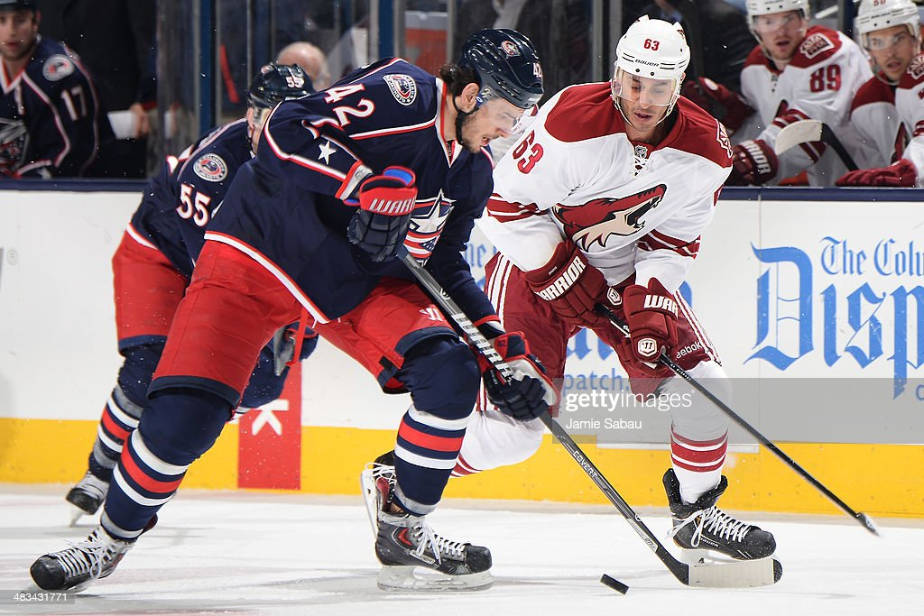 Artem Anisimov #42 of the Columbus Blue Jackets and Mike Ribeiro #63 of the Phoenix Coyotes battle for possession of the puck during the first period on April 8, 2014 at Nationwide Arena in Columbus, Ohio.