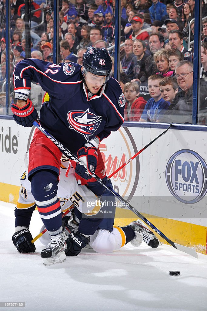 Artem Anisimov #42 of the Columbus Blue Jackets attempts to control the puck after colliding with Victor Bartley #64 of the Nashville Predators during the first period on April 27, 2013 at Nationwide Arena in Columbus, Ohio.