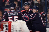 Artem Anisimov of the Columbus Blue Jackets celebrates his third period goal with Mark Letestu and Matt Calvert during the game against the Calgary...
