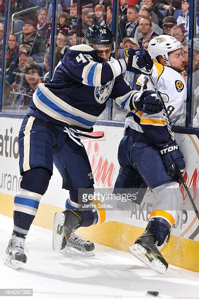 Artem Anisimov of the Columbus Blue Jackets checks Kevin Klein of the Nashville Predators into the boards during the first period on March 19 2013 at...