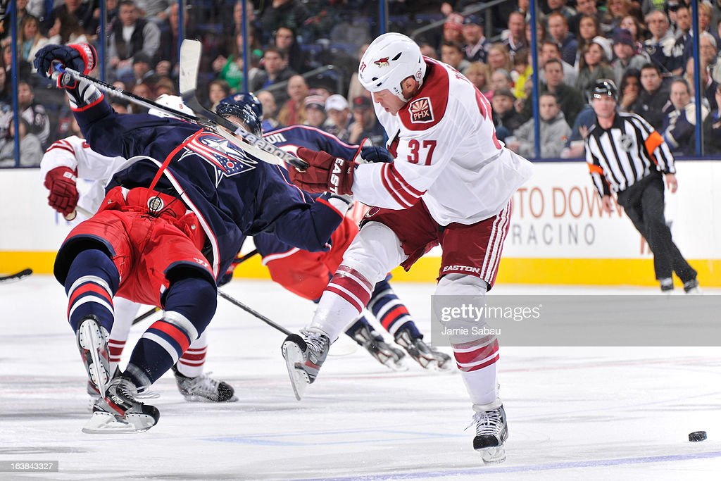 Artem Anisimov #42 of the Columbus Blue Jackets is checked by Raffi Torres #37 of the Phoenix Coyotes during the third period on March 16, 2013 at Nationwide Arena in Columbus, Ohio. Columbus defeated Phoenix 1-0 in a shootout.