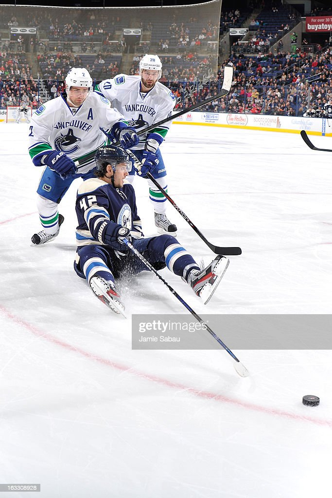 <a gi-track='captionPersonalityLinkClicked' href=/galleries/search?phrase=Artem+Anisimov&family=editorial&specificpeople=543215 ng-click='$event.stopPropagation()'>Artem Anisimov</a> #42 of the Columbus Blue Jackets loses his balance, but still sweeps the puck from <a gi-track='captionPersonalityLinkClicked' href=/galleries/search?phrase=Dan+Hamhuis&family=editorial&specificpeople=204213 ng-click='$event.stopPropagation()'>Dan Hamhuis</a> #2 of the Vancouver Canucks and Chris Higgins #20 of the Vancouver Canucks during the third period on March 7, 2013 at Nationwide Arena in Columbus, Ohio. Columbus beat Vancouver 2-1 in overtime.