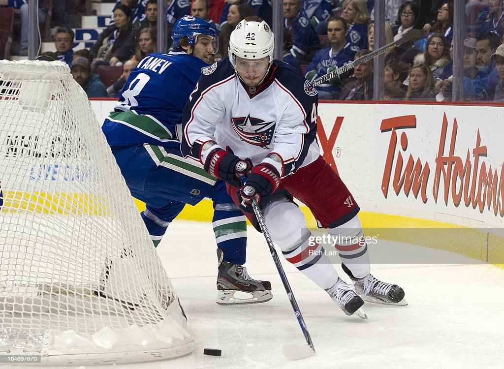 Artem Anisimov #42 of the Columbus Blue Jackets skates with the puck from behind the net after breaking free from Chris Tanev #8 of the Vancouver Canucks during the third period in NHL action on March 26, 2013 at Rogers Arena in Vancouver, British Columbia, Canada.