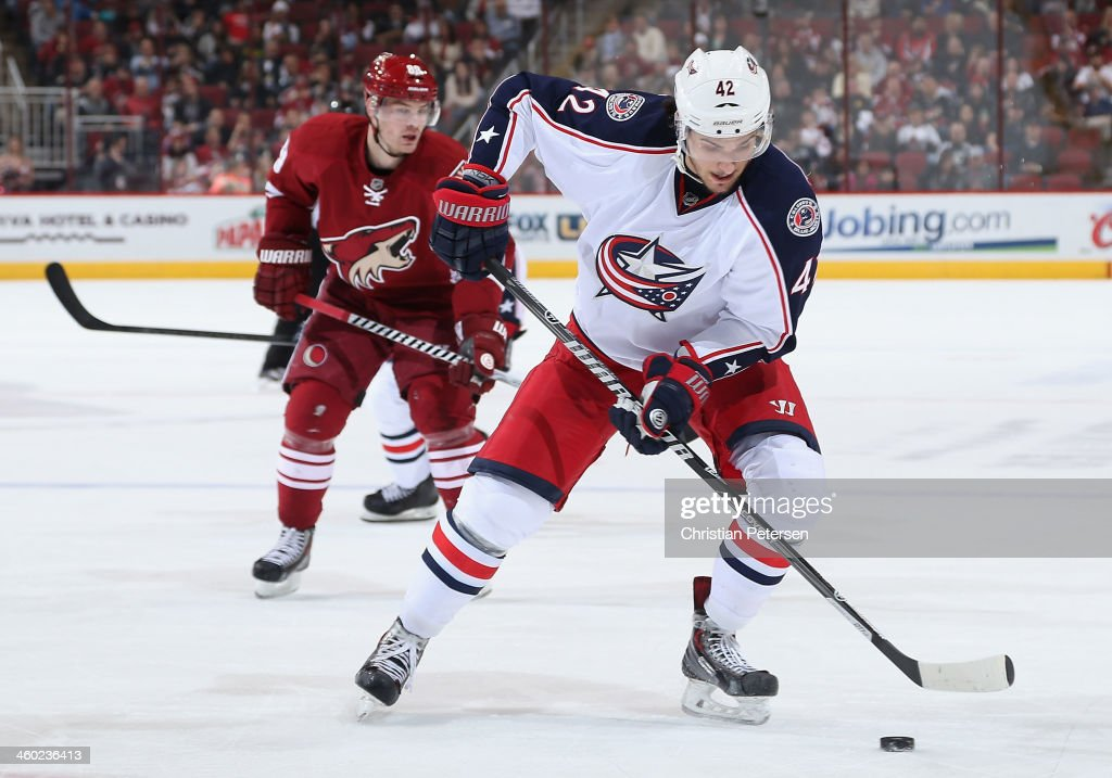 Artem Anisimov #42 of the Columbus Blue Jackets skates with the puck ahead of Mikkel Boedker #89 of the Phoenix Coyotes during the second period of the NHL game at Jobing.com Arena on January 2, 2014 in Glendale, Arizona.
