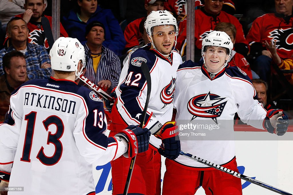 Artem Ansimov #42, Matt Calvert #11 and <a gi-track='captionPersonalityLinkClicked' href=/galleries/search?phrase=Cam+Atkinson&family=editorial&specificpeople=6270272 ng-click='$event.stopPropagation()'>Cam Atkinson</a> #13 of the Columbus Blue Jackets celebrate a goal against the Calgary Flames on March 29, 2013 at the Scotiabank Saddledome in Calgary, Alberta, Canada.