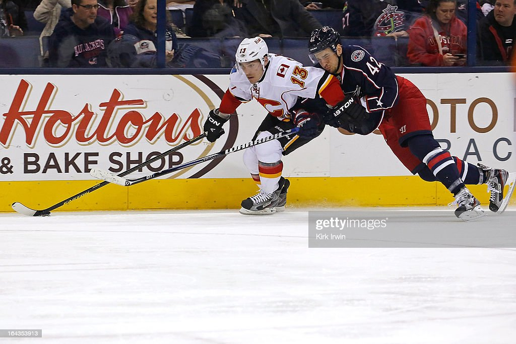 Artem Ansimov #42 of the Columbus Blue Jackets attempts to knock the puck away from Mike Cammalleri #13 of the Calgary Flames during the third period on March 22, 2013 at Nationwide Arena in Columbus, Ohio. Columbus defeated Calgary 5-1.