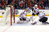 Artem Ansimov of the Columbus Blue Jackets gets the puck past Antti Raanta Niklas Hjalmarsson and Brent Seabrook of the Chicago Blackhawks fall on a...