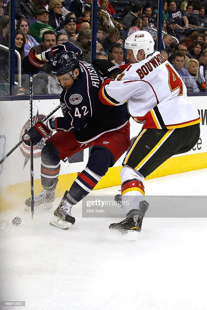 Artem Ansimov #42 of the Columbus Blue Jackets is checked by Jay Bouwmeester #4 of the Calgary Flames while chasing after a loose puck during the second period on February 7, 2013 at Nationwide Arena in Columbus, Ohio.