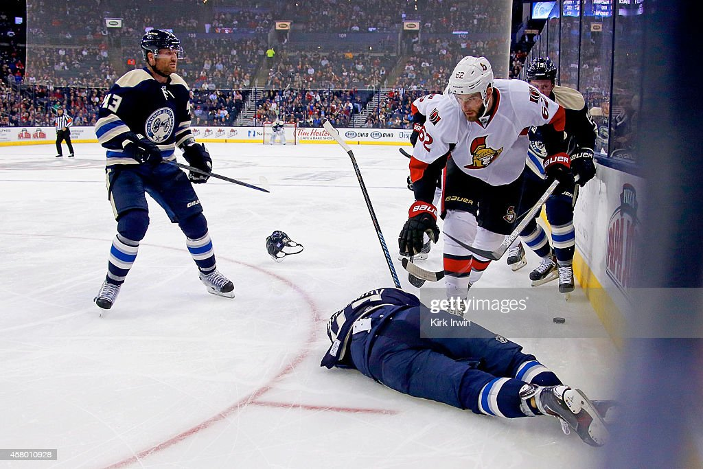 Artem Ansimov #42 of the Columbus Blue Jackets lays on the ice after being hit by <a gi-track='captionPersonalityLinkClicked' href=/galleries/search?phrase=Eric+Gryba&family=editorial&specificpeople=570539 ng-click='$event.stopPropagation()'>Eric Gryba</a> #62 of the Ottawa Senators during the second period on October 28, 2014 at Nationwide Arena in Columbus, Ohio. Gryba was given a five minute major penalty and ten minute game misconduct for the hit, and Anisimov did not return to the ice.