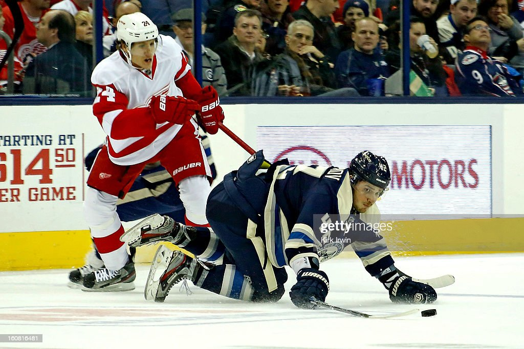 Artem Ansimov #42 of the Columbus Blue Jackets looses his footing while battling for control of a loose puck with Damien Brunner #24 of the Detroit Red Wings on February 2, 2013 at Nationwide Arena in Columbus, Ohio.