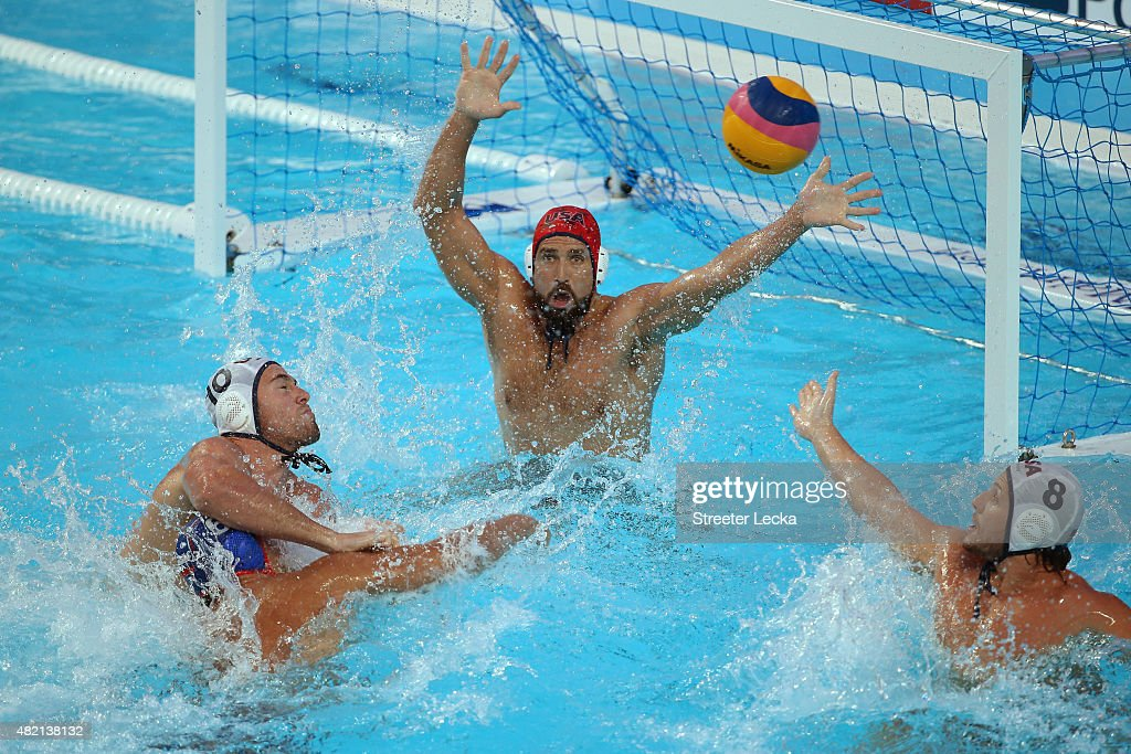 Artem Ashaev of Russia shoots as he is challenged by Bret Bonanni of the United States with goalkeeper <a gi-track='captionPersonalityLinkClicked' href=/galleries/search?phrase=Merrill+Moses&family=editorial&specificpeople=1025270 ng-click='$event.stopPropagation()'>Merrill Moses</a> of the United States looking on in the Men's Water Polo Preliminary Round group B match between United States and Russia on day three of the 16th FINA World Championships at the Water Polo Arena on July 27, 2015 in Kazan, Russia.