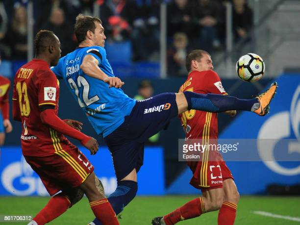 Artem Dzuyba of FC Zenit St Petersburg vies for the ball with Stophira Sunzu and Alexandru Bourceanu of FC Arsenal Tula during the during the Russian...