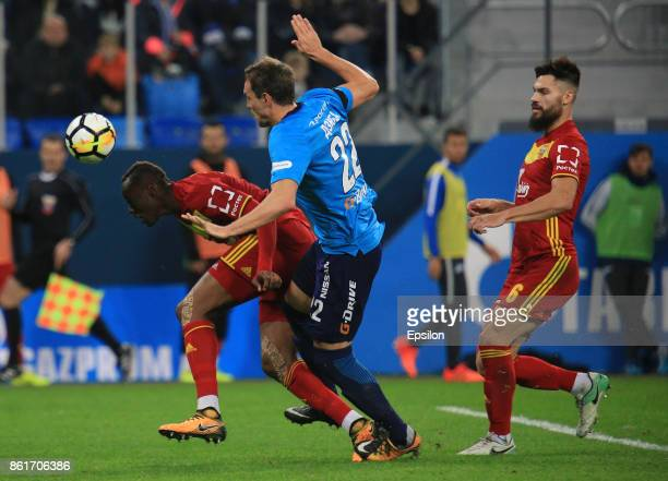 Artem Dzuyba of FC Zenit St Petersburg vies for the ball with Stophira Sunzu and Maxim Belyaev of FC Arsenal Tula during the during the Russian...