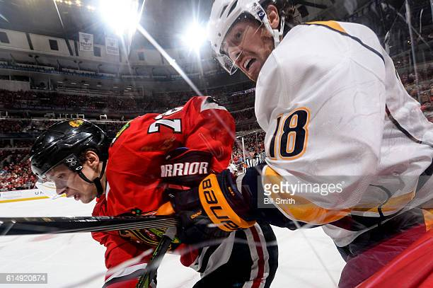 Artemi Panarin of the Chicago Blackhawks and James Neal of the Nashville Predators follow the puck around the boards in the second period at the...