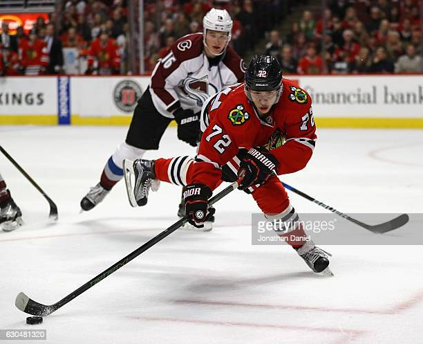Artemi Panarin of the Chicago Blackhawks controls the puck in front of Nikita Zadorov of the Colorado Avalanche at the United Center on December 23...