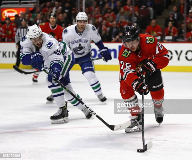 Artemi Panarin of the Chicago Blackhawks is pressured by Michael Chaput of the Vancouver Canucks at the United Center on March 21 2017 in Chicago...