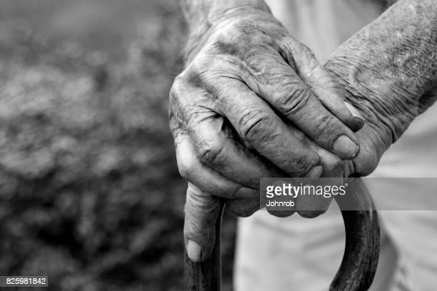 Arthritic Hands resting on cane in black and white. Looking down view at hands.