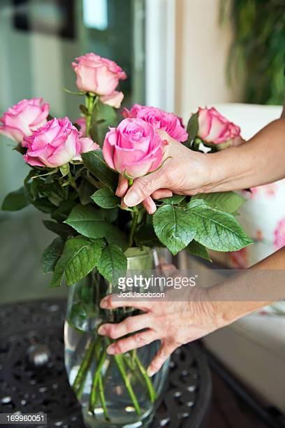 Arthritis: Arthritic senior hands holding a flower vase