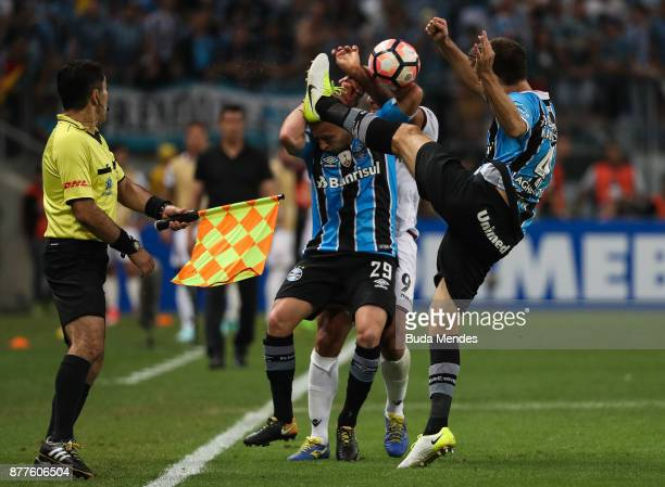 Arthur and Walter Kannemann of Gremio struggle for the ball with Jose Sand of Lanus during a first leg match between Gremio and Lanus as part of Copa...