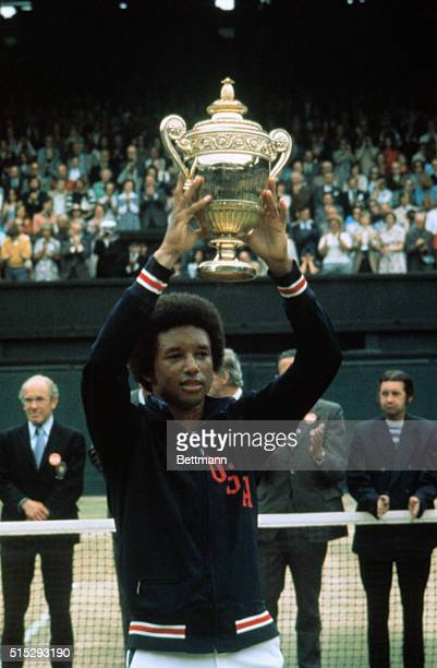 Arthur Ashe holds up his Wimbledon trophy after defeating Jimmy Connors in the Men's Singles championship 61 61 57 64