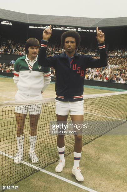 Arthur Ashe poses for cameras and gestures to the camera next to Jimmy Connors at the net after the match at the Wimbledon Open in July of 1975 in...