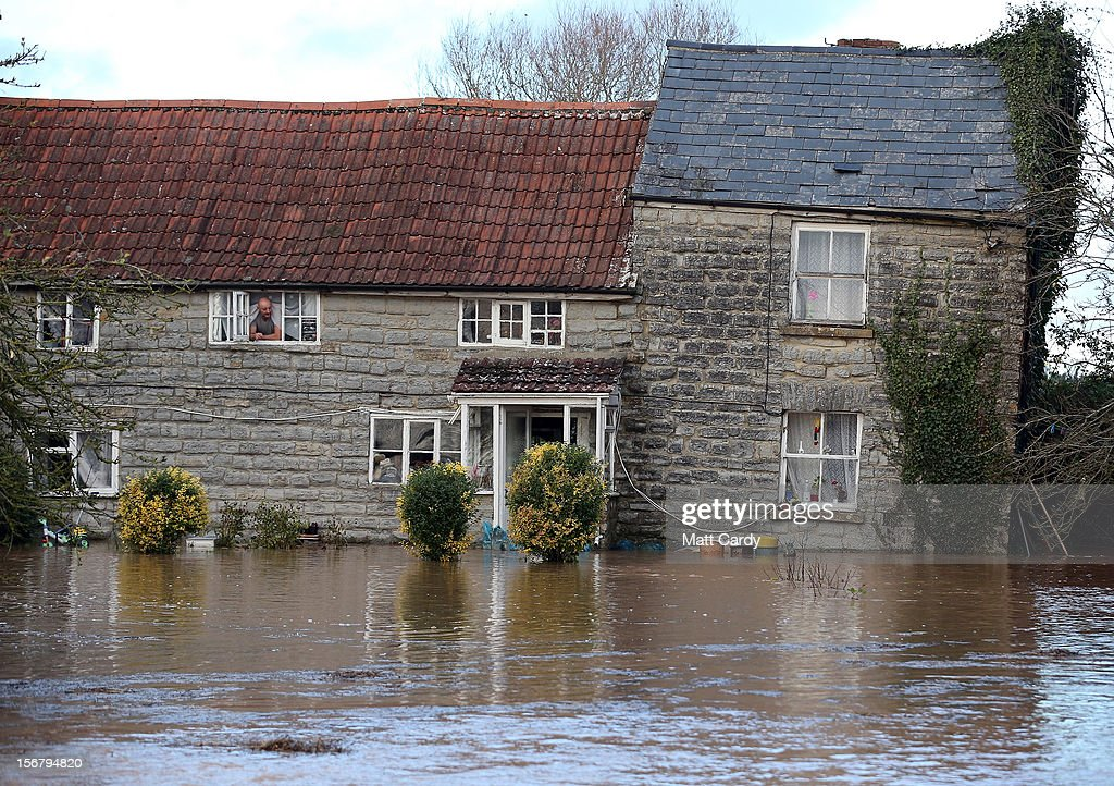 Arthur Dziewicki looks at the flood water lapping at the front door of his cottage that has been flooded close to the village of North Curry on November 21, 2012 near Taunton, England. Heavy rain overnight has brought widespread disruption to many parts of the UK particularly in the Somerset and Wiltshire and weather forecasters have warned of more wet and windy weather to come.